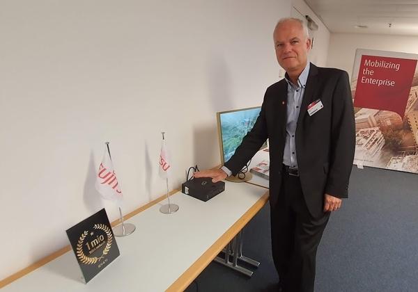 """רענן ביבר, מנכ""""ל פוג'יטסו ישראל, מניח ידו על הנייח הננסי של פוג'יטסו G558 הנחשב למחשב הנייח הקטן בעולם. צילום: פלי הנמר"""